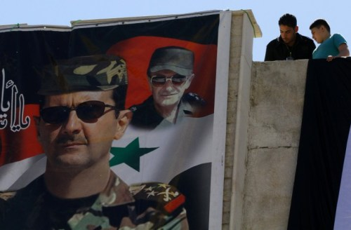 Syrians look down at a poster of Syrian President Bashar al-Assad (L) and his late father and predecessor Hafez al-Assad in Damascus, as they watch the tourist train pass following the re-opening ceremony of the rail route between two neighbourhoods in the Syrian capital, Raboeh and Dumar, on May 1, 2015. AFP PHOTO / LOUAI BESHARA (Photo credit should read LOUAI BESHARA/AFP/Getty Images)
