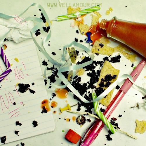 A mess of dirt, food, and office supplies splattered across a countertop