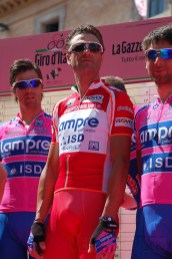 Ale arrives. Tall, handsome, tanned, hair gelled back, shades atop his head, the red Punti jersey on his back, that loose limbed slouch.