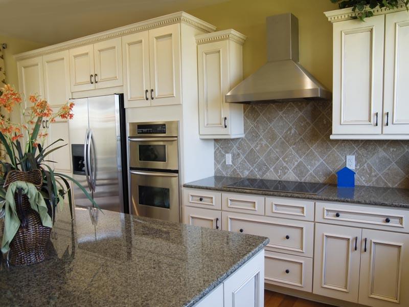 granite kitchen tops and travertine tile as splashback