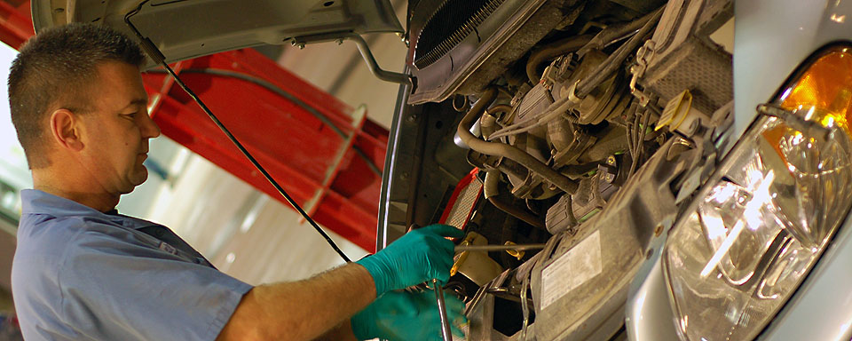 Image showing VEMA repair technician working with the hood open on a VEMA managed vehicle