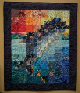 """My first quilt 'Dolphin Sunset' completed Sept. 1998. Took a class on watercolor quilts at The Cotton Ball in Morro Bay. Everyone else did a case of flowers, I did a dolphin."""