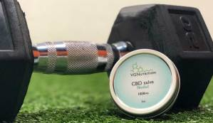 menthol CBD salve resting in front of a dumbell