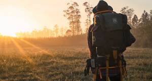 man with hiking back pack on standing in field looking at sunset over the horizon