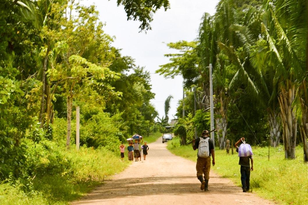 People walk down a dirt road in Guatemala