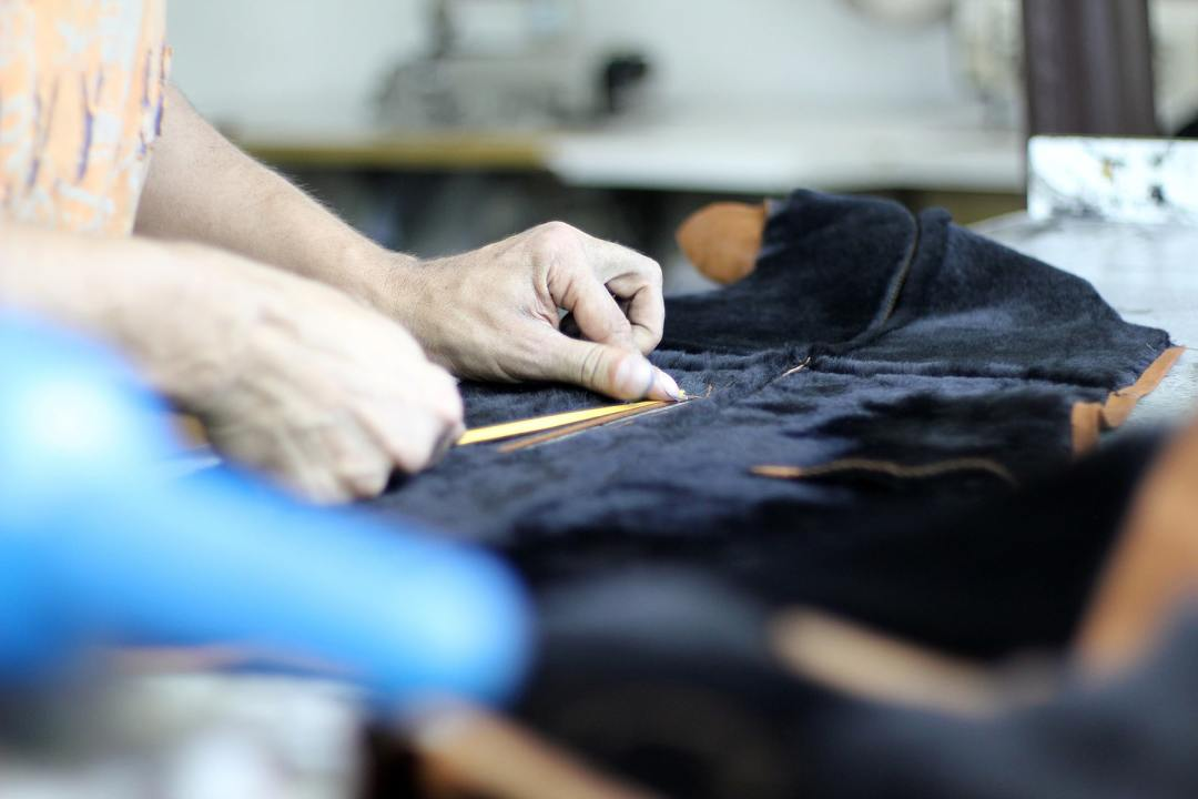 A worker measures a garment