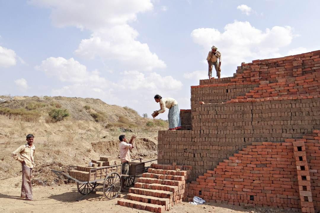 Construction workers in India pass bricks to one another