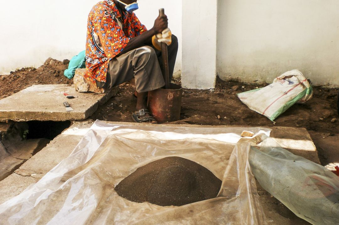 A worker sifting coltan