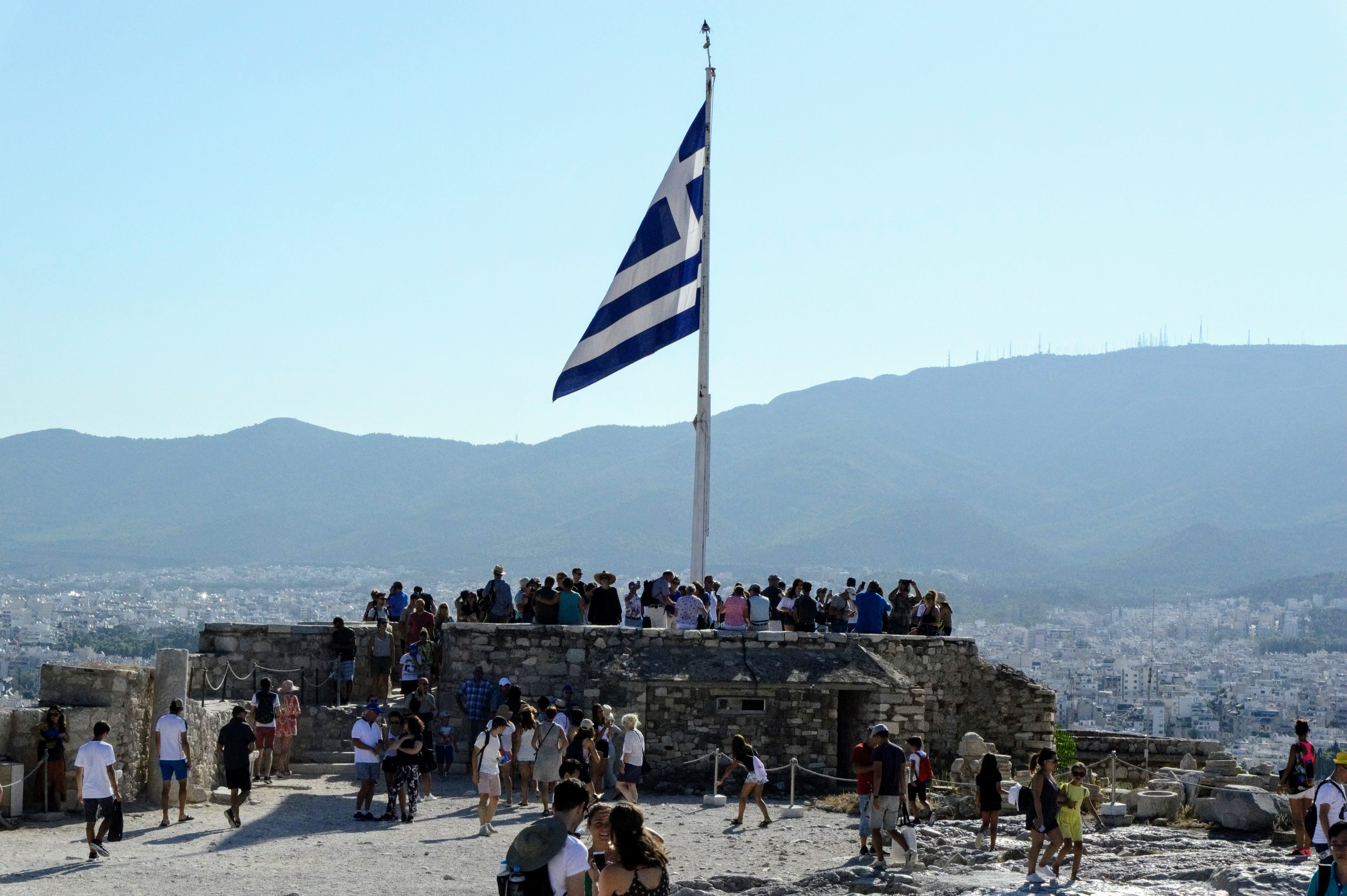 Flag on the top of Acropolis of AthensHekatompedon Temple - Acropolis of Athens - Athens, Greece, Europe - Honeymoon Part 1 - Athens is a beautiful capital city rich with history. With it's impressive Acropolis and quaint pedestrian streets, we headed here for our Honeymoon Part 1! Veritru Travel Blog