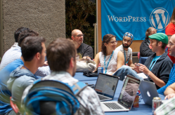 The Happiness Bar at WordCamp Montreal 2015, people sitting around a table talking with laptops