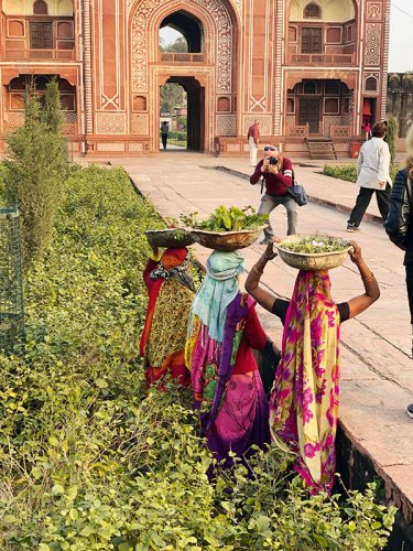 A Tourist photographs local gardeners during sunset at Itimad-ud-Daulah's tomb