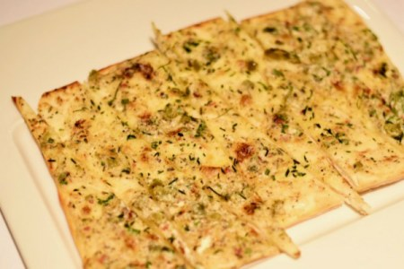 Olio house bread topped with herb oil, feta and cheese