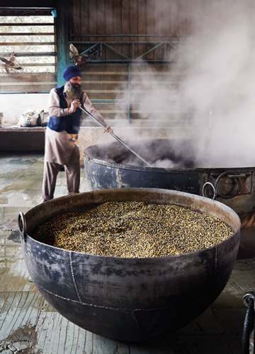 A cauldron of raw lentils and another of dal being stirred