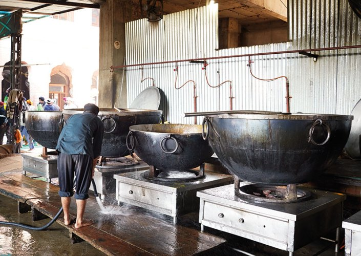 Washing of some of the massive cauldrons used to cook and feed the masses