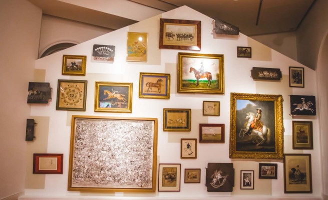 Wall with paintings from the Émile Hermès collection including the 'Hitched carriage and waiting groom' a 19th century drawing by French artist Alfred de Dreux that inspired the Hermès logo