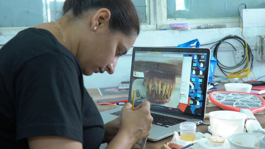 """Zuby Johal painting the prosthetic teeth for a character in """"Ghost Stories"""""""