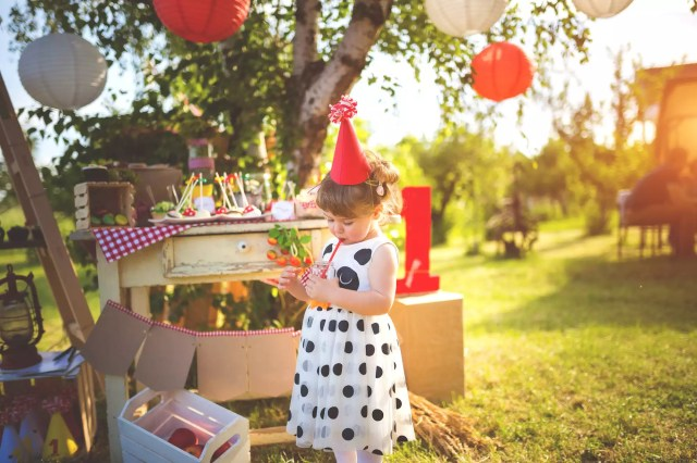 little girl in party hat drinking from cup