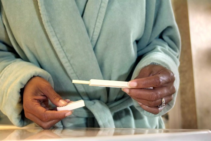 Woman taking the cap off a pregnancy test