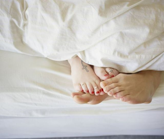 Young Couple In Bed Feet Touching Allusion To Female Orgasm And Fertility