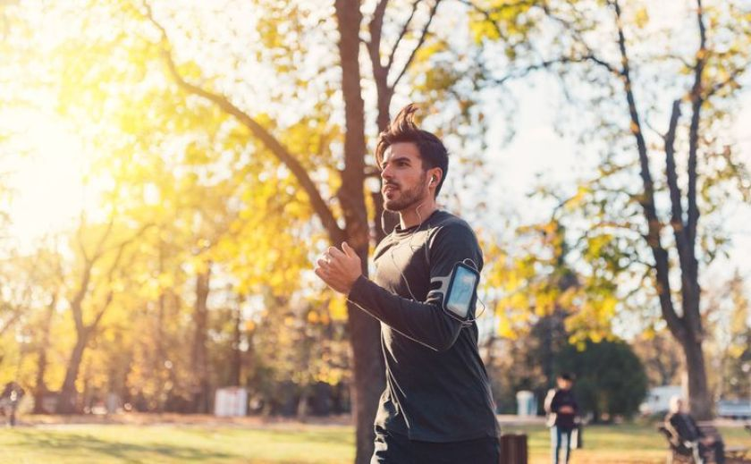 Sportsman jogging in the autumn park