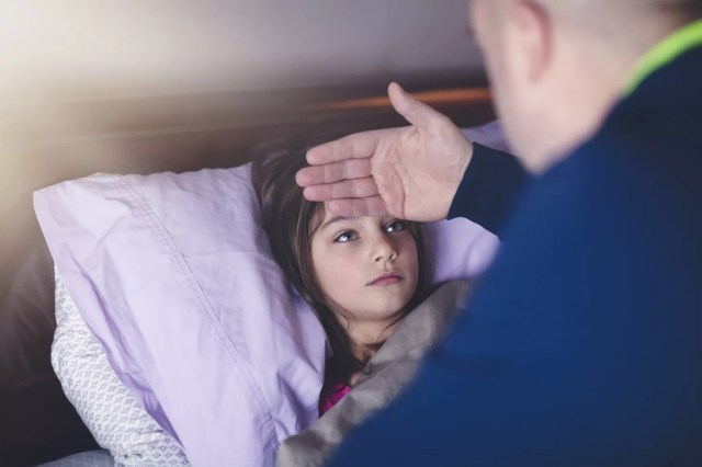 Father checking daughter's forehead for fever