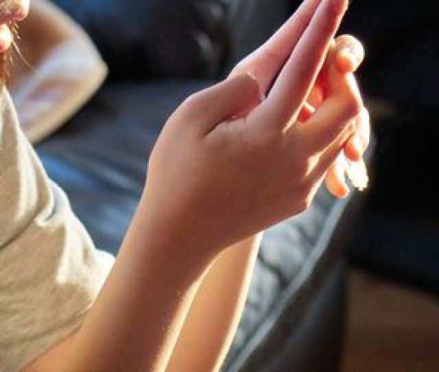 Cropped Image Of Girl Using Mobile Phone While Sitting On Sofa At Home