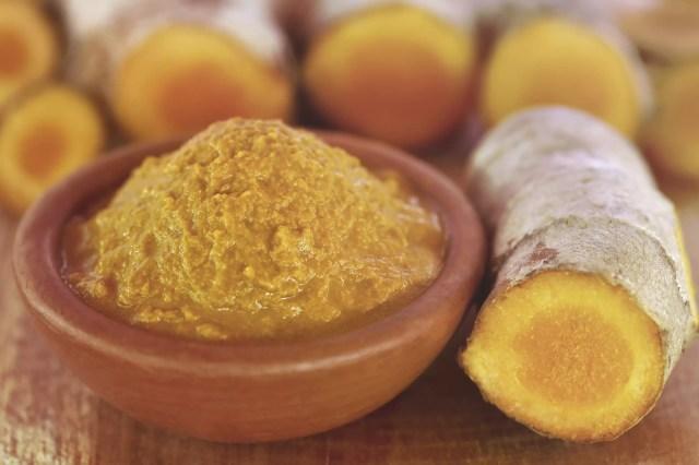 Fresh turmeric in a bowl and turmeric root