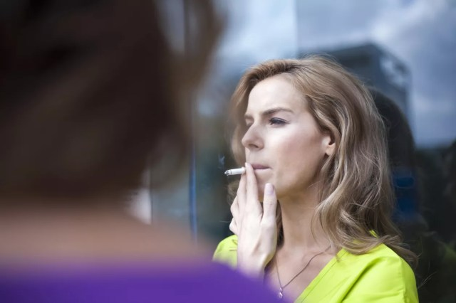 Photo of a woman smoking outside her office.