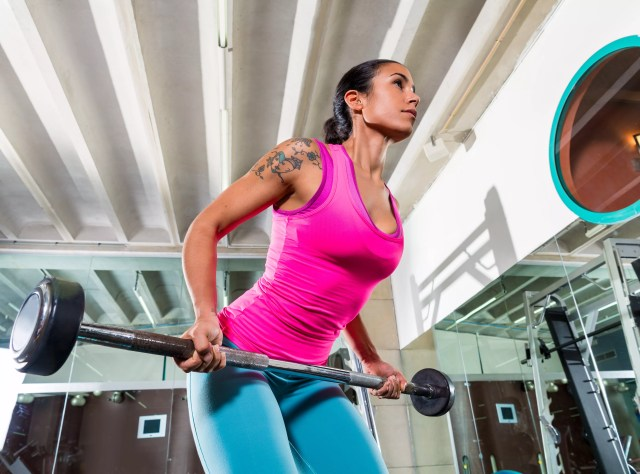 A woman does a bent row exercise with a straight back and engaged core muscles.