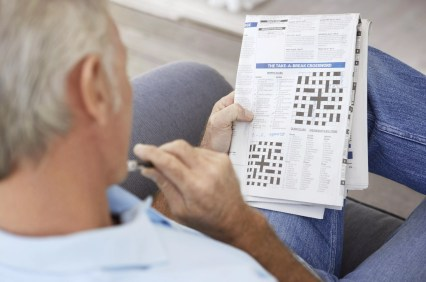 Senior Man Contemplating a Newspaper Crossword