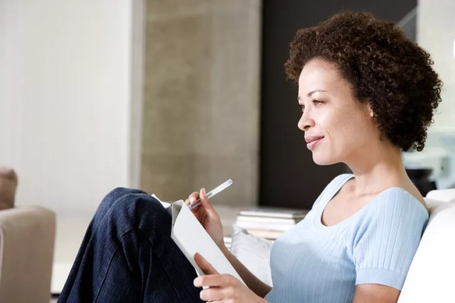 Woman writing a diary or journal, relaxing at home