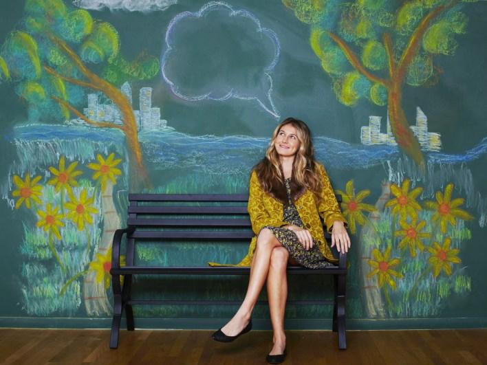 امرأة تجلس على مقعد أمام جدارية طباشير