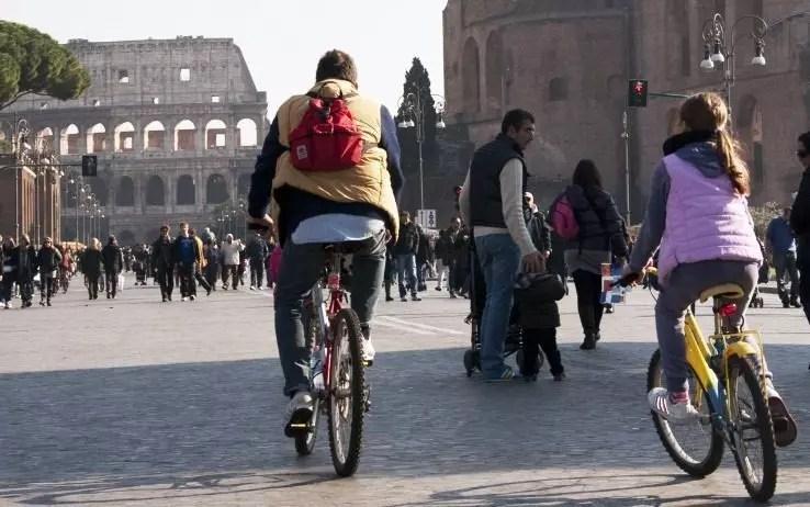Una bimba con il papà in bicicletta in via dei Fori Imperiali, sullo sfondo il Colosseo, 20 novembre 2011, Roma.  Freddo e sole hanno accolto la prima domenica a piedi nella città. Da questa mattina alle 8.30 è scattato il blocco del traffico nella capitale. Fino alle 17.30 la circolazione sara' vietata all'interno della fascia verde, un po' meno ampia del Grande raccordo anulare. Un provvedimento preso dal Campidoglio per l'eccesso di polveri sottili nell'aria. Migliaia di persone, tra romani e  turisti, su via dei Fori Imperiali, oggi pedonalizzata in occasione dello stop alle auto deciso dal Campidoglio.    Da Piazza Venezia al Colosseo e' un'unica 'scia umana' in movimento: chi su biciclette, chi facendo jogging, chi passeggiando in una domenica autunnale con un cielo sereno e un sole splendido. ANSA/ROSANNA DI BARTOLOMEO/DBA