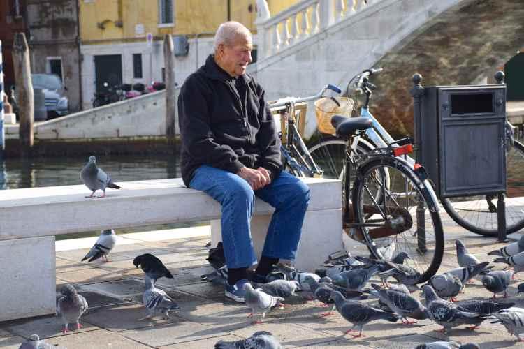 Un signore da da mangiare ai piccioni nel centro storico di Chioggia