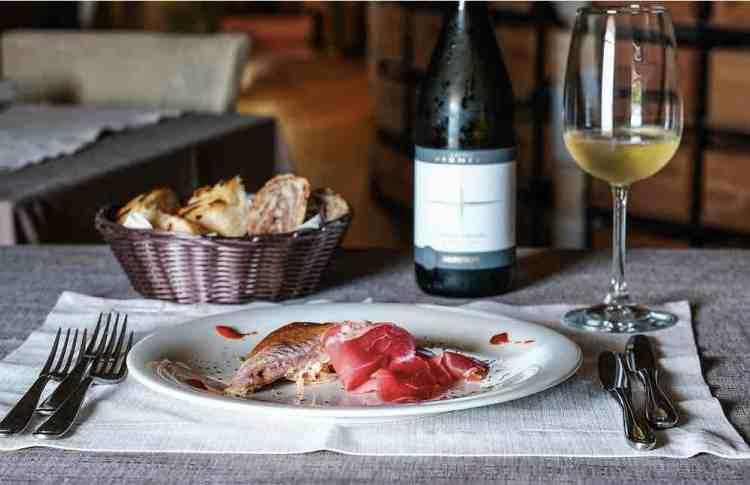 uno squisito piatto accompagnato dal vino tipico del garda trentino