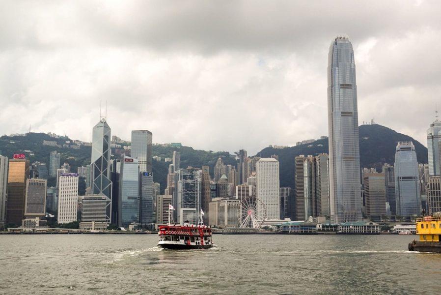 Ferry all'interno della baia di Hong Kong con skyline dei grattacieli