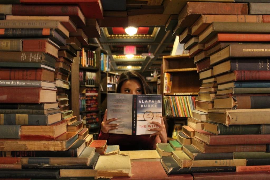 una ragazza in una biblioteca che legge libri al posto di acquistarli per risparmiare soldi