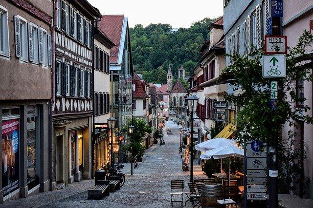 vista de una calle en un pueblo en Alemania con restaurantes y sillas en la calle