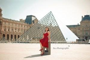 Mujer vestido rojo sentada enfrente del museo louvre