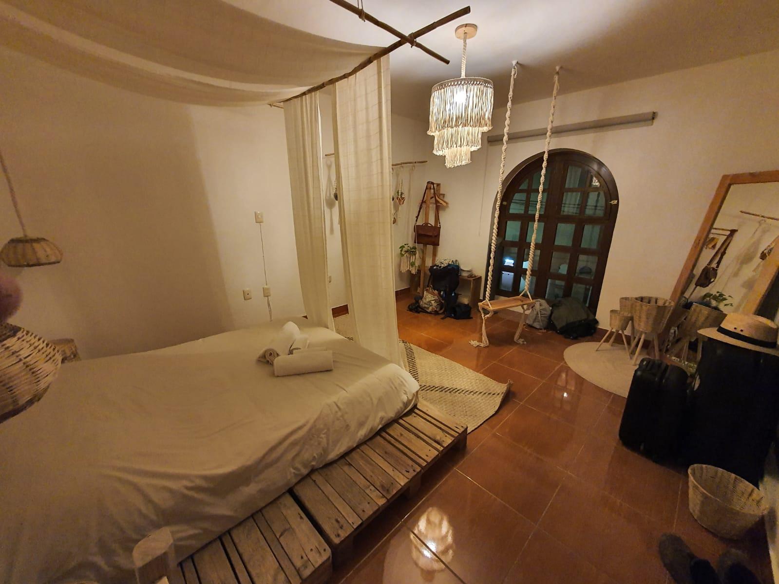habitación Airbnb en Oaxaca decorada con tejidos a mano y un columpio en el medio