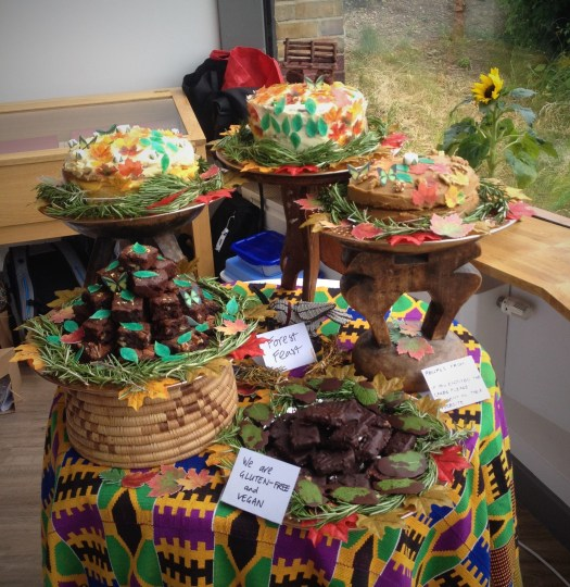 three cakes and two plates of brownies, covered with edible leaves