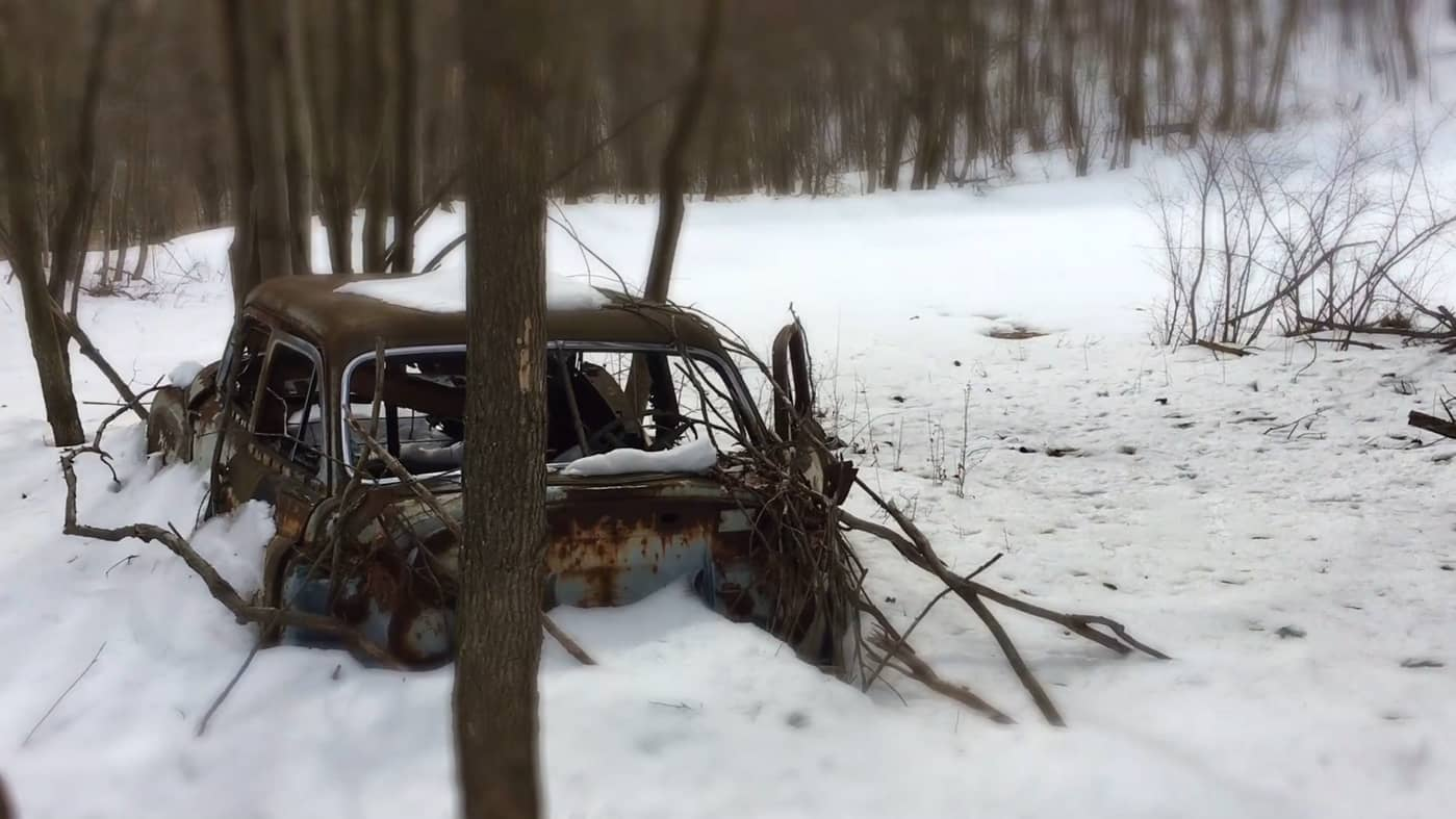 "still from ""55"" showing a junker car in the middle of a snowy field"