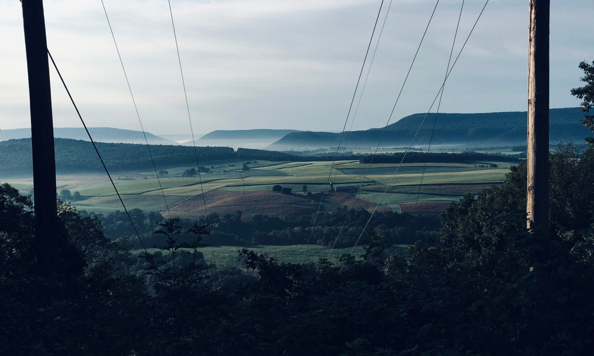 view of a farm valley with fog and wooded ridges beyond