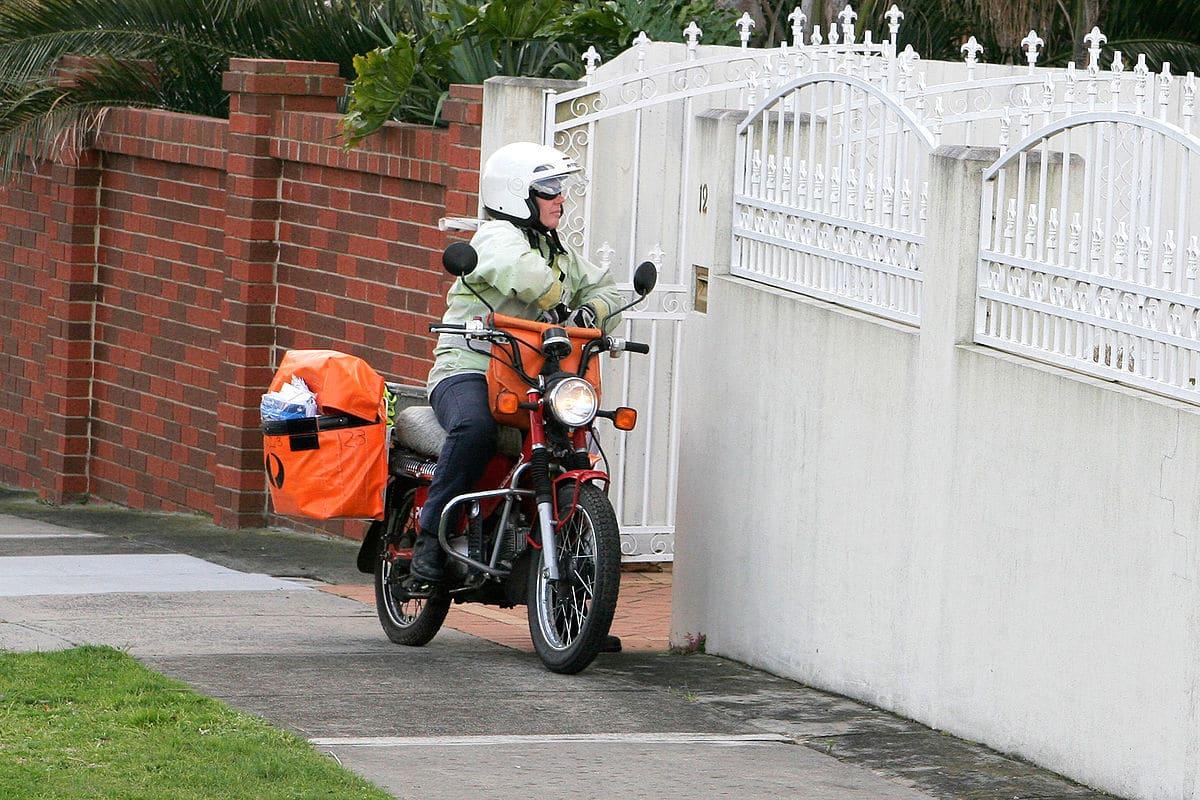 Tukang Post Menggunakan Sepeda Motor Untuk Mengantar Paket, Dokumen, Dan Surat
