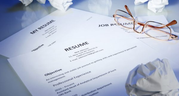 Closeup of resume with glasses on blue background