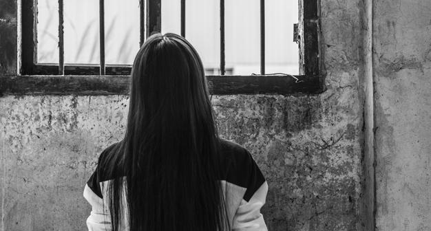 vista-trasera-de-mujer-solitaria-mirando-hacia-fuera-desde-la-ventana_1205-203