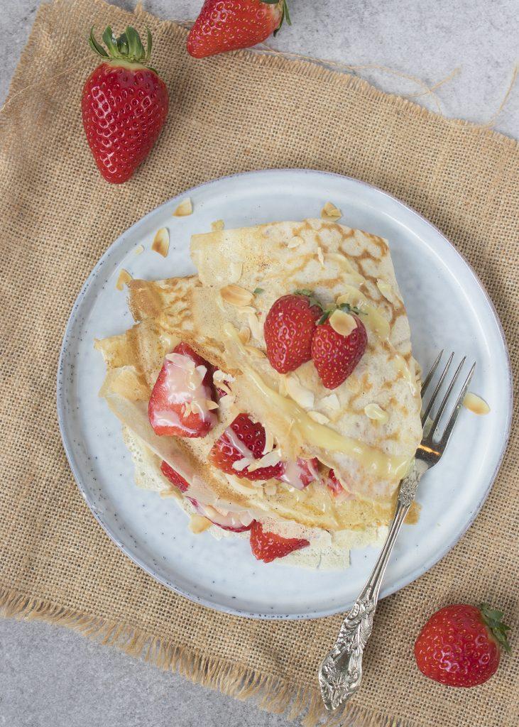 Crêpes met aardbeien, witte chocolade en geschaafde amandelen