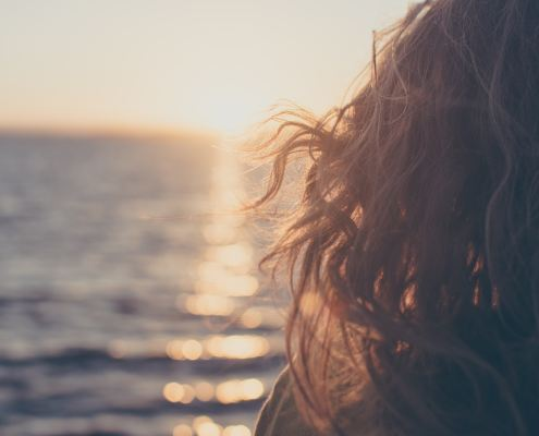 A woman with curly brown hair watches the sun set over the ocean