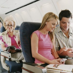 A couple and older person relaxing on a flight