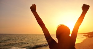 Young women with arms in the air celebrating as the sun rises over the sea